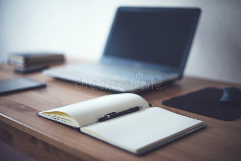 Stilvoller Freiberuflerarbeitsplatz mit offener Notizblockarbeit des Laptops bearbeitet zu Hause oder Studiobüroarbeitsplatz stockfotos