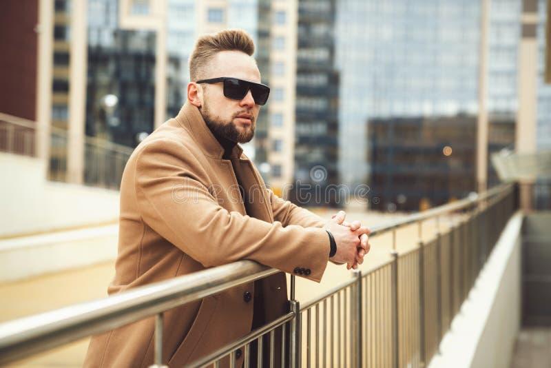 Stilvoller Geschäftsmann in der Sonnenbrille lehnte sich auf einem Eisen, das Hintergrund des Geschäftszentrums mit der Eisenbahn lizenzfreies stockfoto