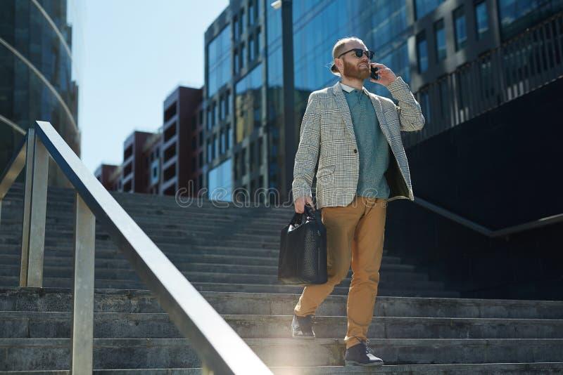 Stilvoller Geschäftsmann, der Telefon auf Bewegung verwendet lizenzfreies stockbild