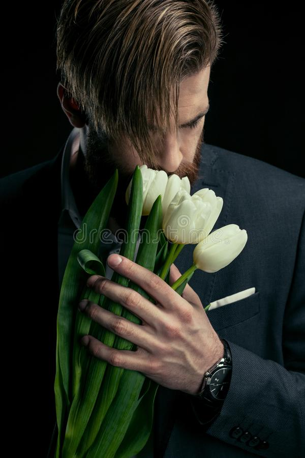 Stilvoller Geschäftsmann im Anzug, der Tulpen am schwarzen Muttertag hält stockfotos