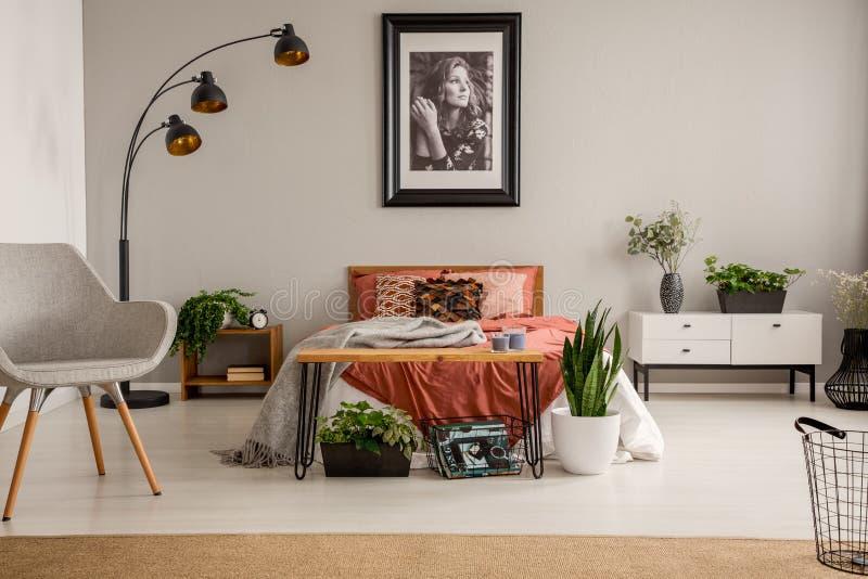 Stilvoller grauer Stuhl, schwarze Lampe, Plakat auf der Wand und Königgrößenbett mit Rostfarbbettwäsche im hellen Schlafzimmer de lizenzfreies stockbild