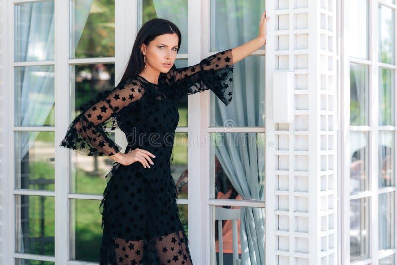 Stilvoller großer Brunette mit den schönen langen Beinen, die draußen in einem schwarzen Kleid nahe einer Glaswand aufwerfen Ein  lizenzfreie stockfotografie