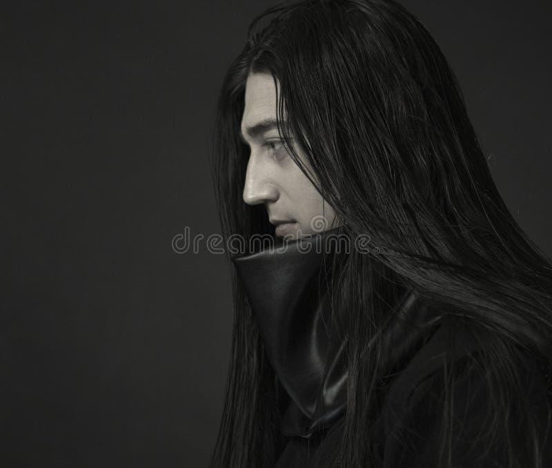 Stilvoller hübscher junger Mann Das Porträt des kaukasischen Mannes Mann in der schwarzen Kleidung mit dem dunklen langen Haar lizenzfreie stockfotos