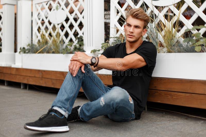 Stilvoller hübscher junger Mann im schwarzen T-Shirt mit Jeans stockbilder