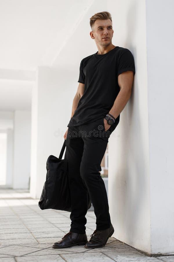 Stilvoller hübscher junger Mann mit einer Frisur in einem schwarzen T-Shirt lizenzfreie stockfotografie