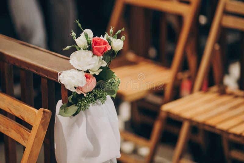 Stilvoller Heiratsdekor von Holzbanken in der Kirche für heiligen Ehestand Schöne Rosen und Tulle-Blumensträuße auf Holzstühlen, lizenzfreie stockbilder