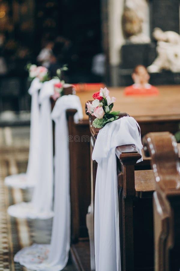 Stilvoller Heiratsdekor von Holzbanken in der Kirche für heiligen Ehestand Schöne Rosen und Tulle-Blumensträuße auf Holzstühlen, stockfotografie