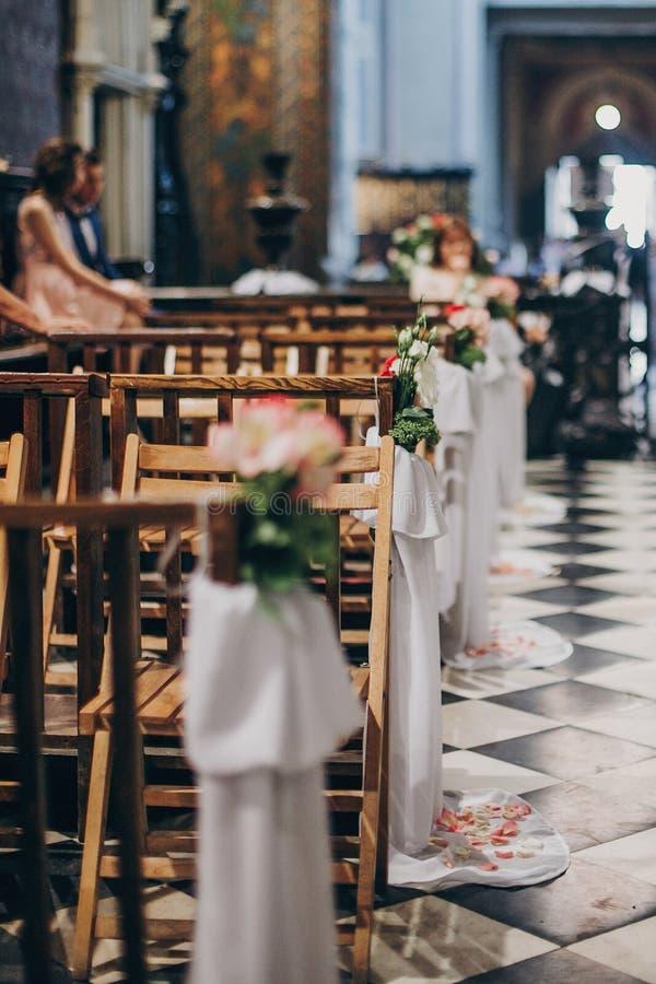 Stilvoller Heiratsdekor von Holzbanken in der Kirche für heiligen Ehestand Schöne Rosen und Tulle-Blumensträuße auf Holzstühlen, stockbilder