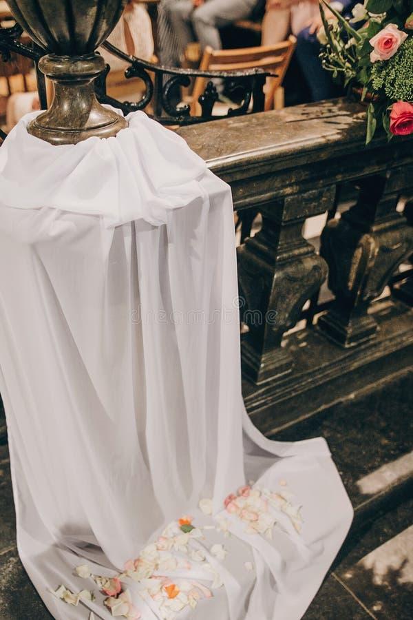 Stilvoller Heiratsdekor von Holzbanken in der Kirche für heiligen Ehestand Schöne Rosen und Tulle-Blumensträuße auf Holzstühlen, stockfoto