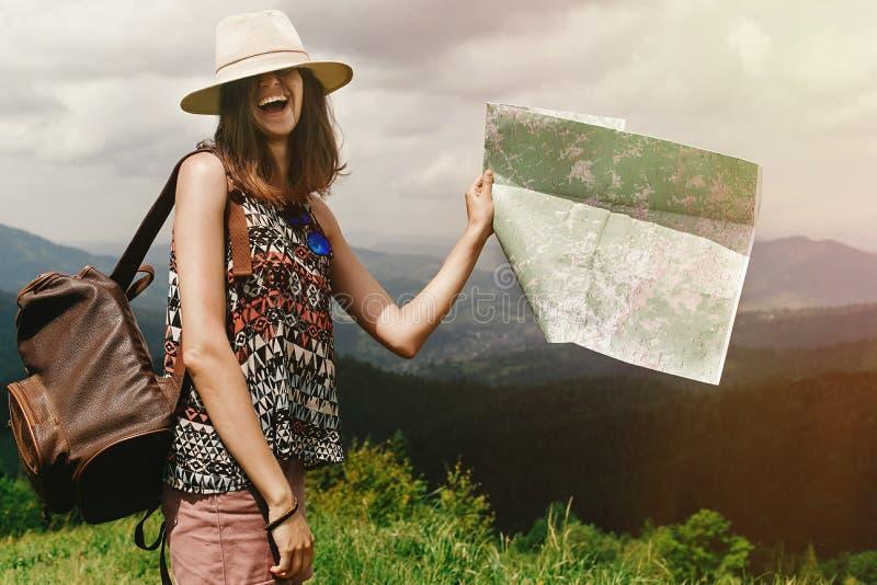 Stilvoller Hippie-Frauenreisender mit dem Rucksack, der Karte und lau hält lizenzfreie stockfotografie