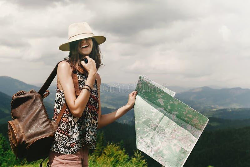 Stilvoller Hippie-Frauenreisender mit dem Rucksack, der Karte und lau hält stockbild
