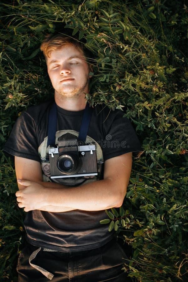 Stilvoller Hippie-Mann mit der Filmfotokamera, die im grünen Gras liegt und in der sonnigen Wiese bei atmosphärischem Sonnenunter stockbild