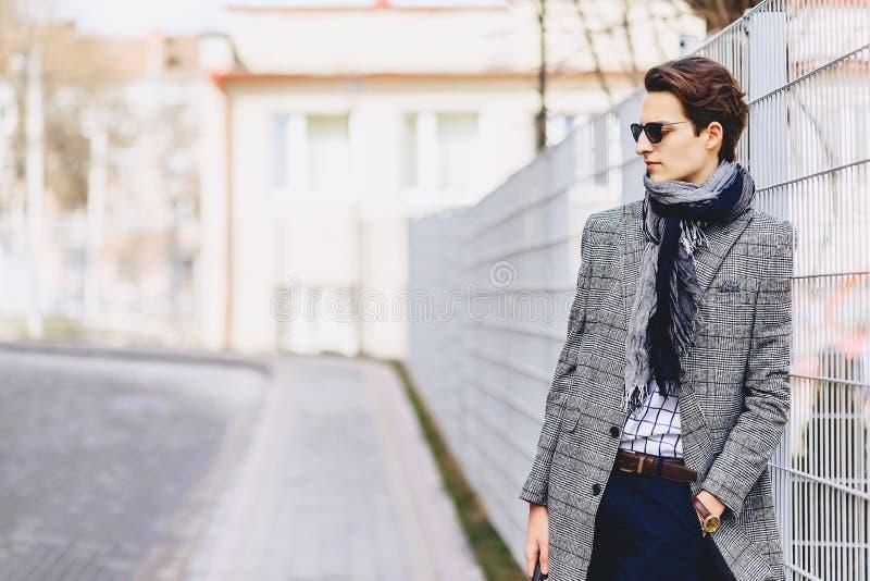Stilvoller Junge in der Sonnenbrille im Mantel mit Aktenkoffer auf Straße lizenzfreie stockbilder