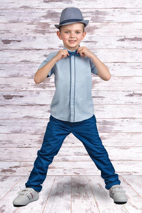 Stilvoller Junge im eleganten Anzug und im Hut Ein Kleinunternehmer Kind-` s Mode lizenzfreies stockfoto