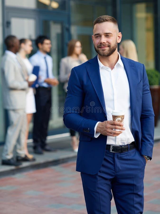 Stilvoller junger Geschäftsmann mit Kaffee außerhalb des Bürogebäudes lizenzfreie stockfotografie