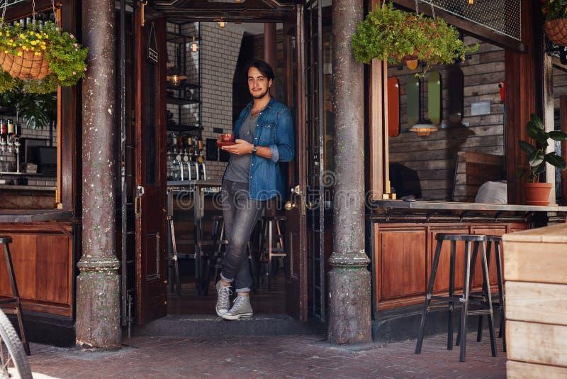 Stilvoller junger Mann an einem Caféeingang lizenzfreie stockfotos