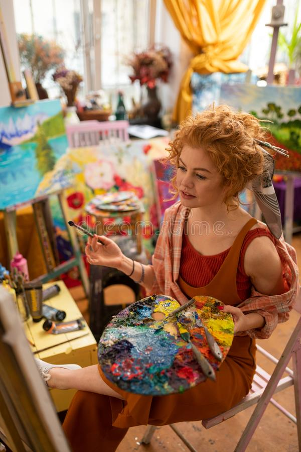 Stilvoller Künstler, der auf Stuhl und Färbungsbild sitzt stockfoto