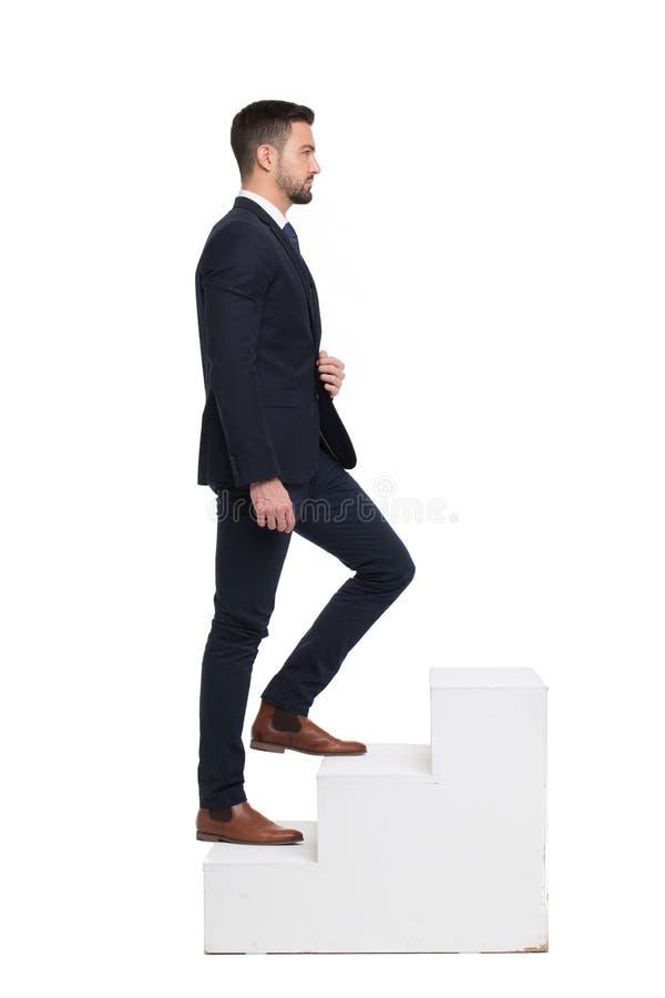 Stilvoller kaukasischer Geschäftsmann, der oben auf die Schritte lokalisiert geht stockbilder