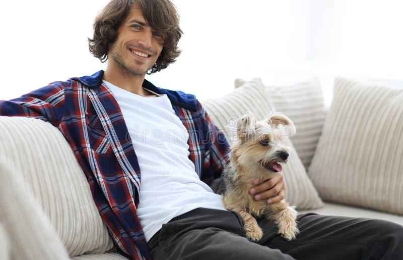 Stilvoller Kerl, der auf der Couch mit seinem Hund sitzt stockfoto