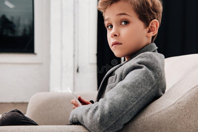 stilvoller kleiner Junge, der im bequemen Lehnsessel sitzt lizenzfreies stockfoto
