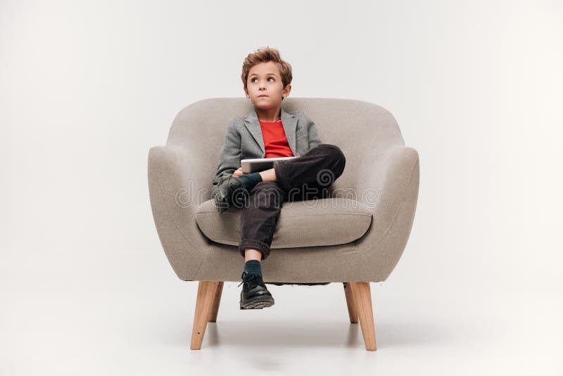 stilvoller kleiner Junge, der im Lehnsessel sitzt lizenzfreies stockbild
