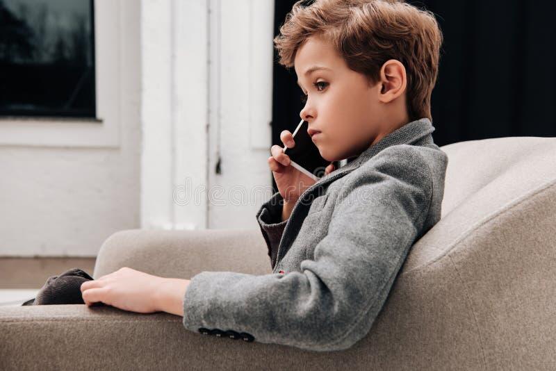 stilvoller kleiner Junge, der im Lehnsessel und in der Unterhaltung sitzt stockfotos