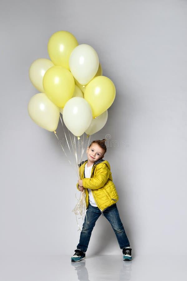 Stilvoller kleiner Junge, der Luftballon lokalisiert auf Weiß hält lizenzfreies stockfoto