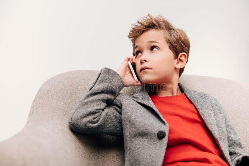 stilvoller kleiner Junge, der telefonisch beim Sitzen im Lehnsessel spricht lizenzfreie stockfotos
