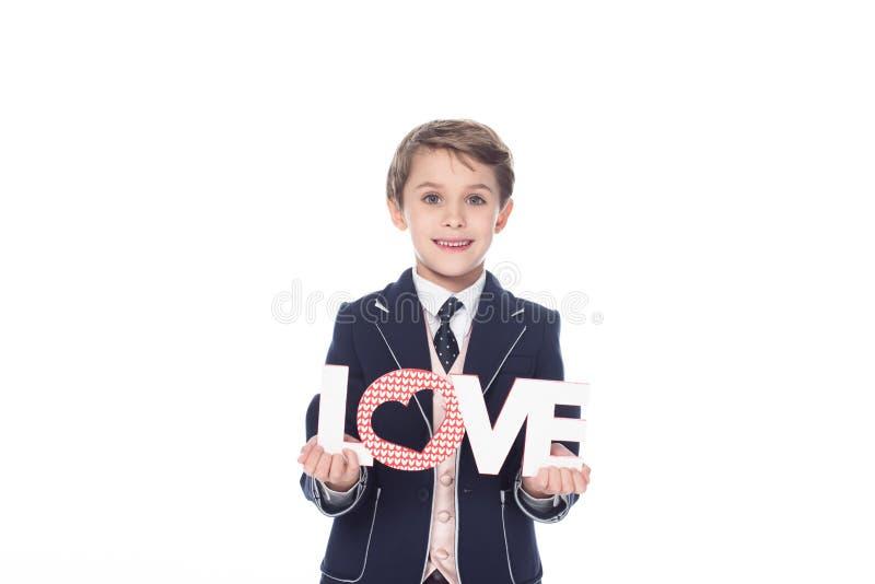stilvoller kleiner Junge, der Wortliebe hält und an der Kamera lächelt lizenzfreie stockfotografie