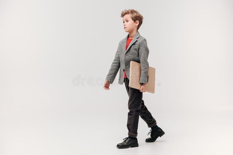 stilvoller kleiner Schüler, der mit großem Buch geht lizenzfreie stockfotos