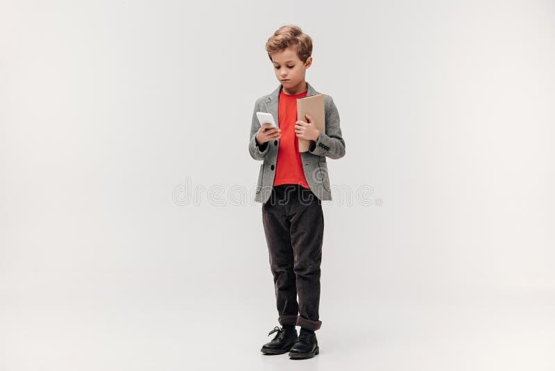stilvoller kleiner Schüler mit Smartphone und Buch lizenzfreies stockfoto
