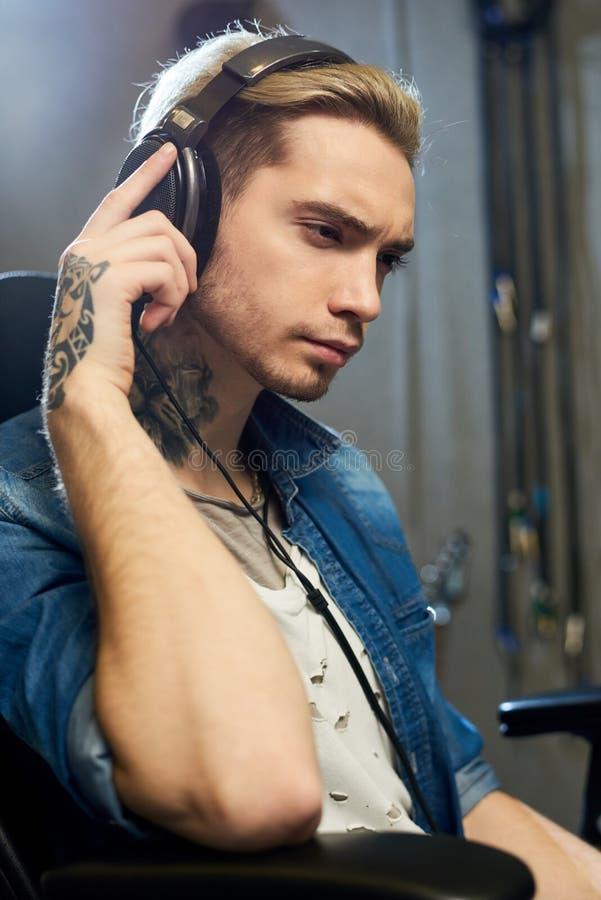 Stilvoller Komponist, der Musik im Studio hört lizenzfreie stockfotografie
