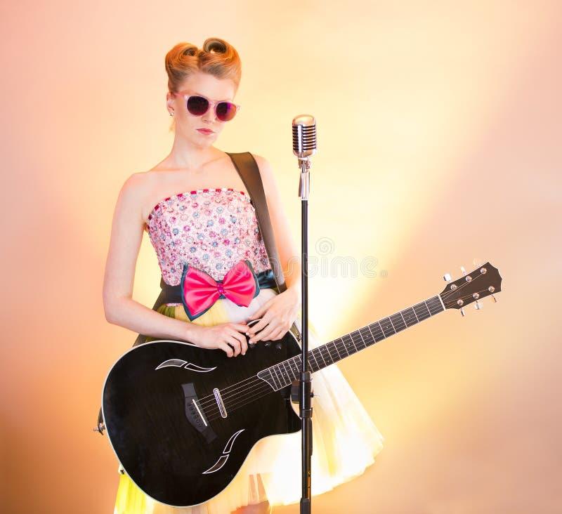 Stilvoller Mädchengitarristsänger in den rosa Gläsern mit schwarzer Gitarre, Weinlesemikrofon Jugendlichmusiker in der lustigen W lizenzfreies stockbild