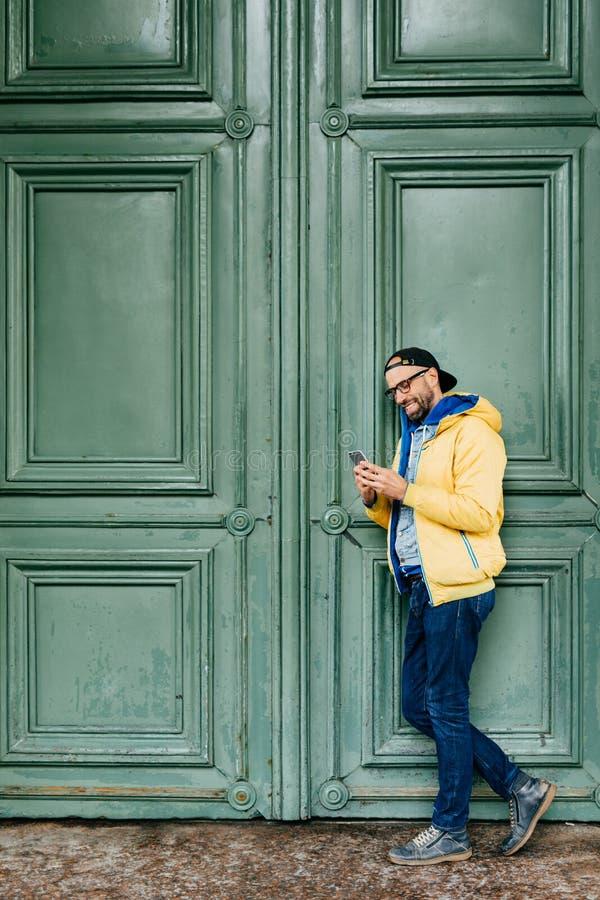 Stilvoller Mann in der schwarzen Kappe und gelben im Anorak, die seitlich gegen den grünen Hintergrund hält Handy lustige Beiträg stockbilder