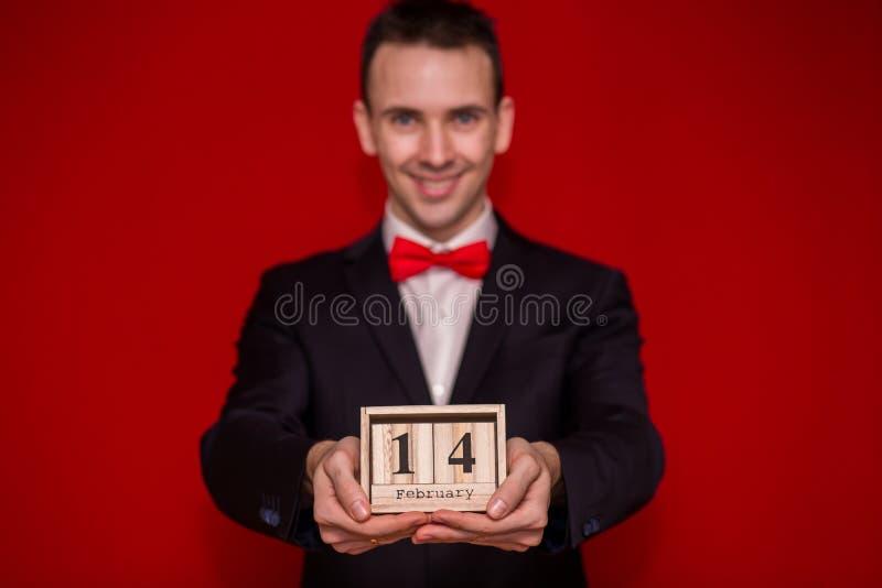 Stilvoller Mann im hölzernen Kalender des Klagengriffs, stellte am 14. Februar mit rotem Hintergrund, Fokus auf Kalender ein lizenzfreie stockfotos