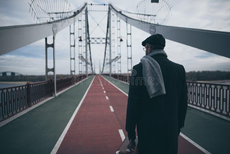 stilvoller Mann im Mantel und im Schal mit Kofferstellung stockfotos
