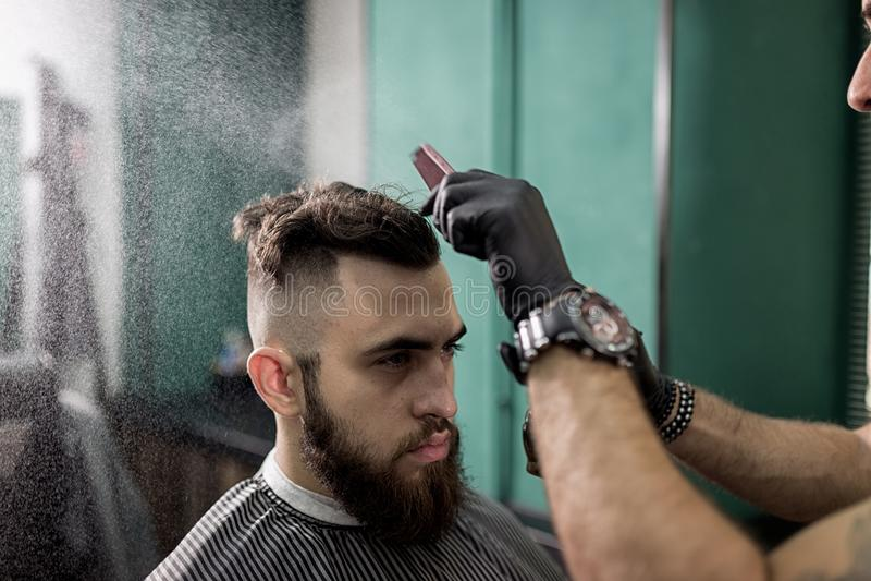 Stilvoller Mann mit einem Bart sitzt an einem Friseursalon Friseur in den schwarzen Handschuhen tut das Sprühen für Frisur stockbilder