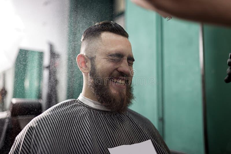 Stilvoller Mann mit einem Bart sitzt und lächelt an einem Friseursalon Friseur in den schwarzen Handschuhen tut das Sprühen für F stockfotografie