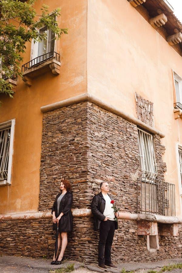 Stilvoller Mann und Frauenstellung von mittlerem Alter nahe der Steinwand des Hauses im Sommer Regenschirmstock und rote Rose stockfotos