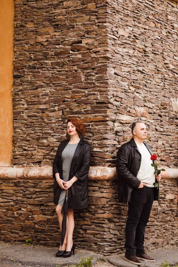 Stilvoller Mann und Frauenstellung von mittlerem Alter nahe der Steinwand des Hauses im Sommer lizenzfreies stockfoto