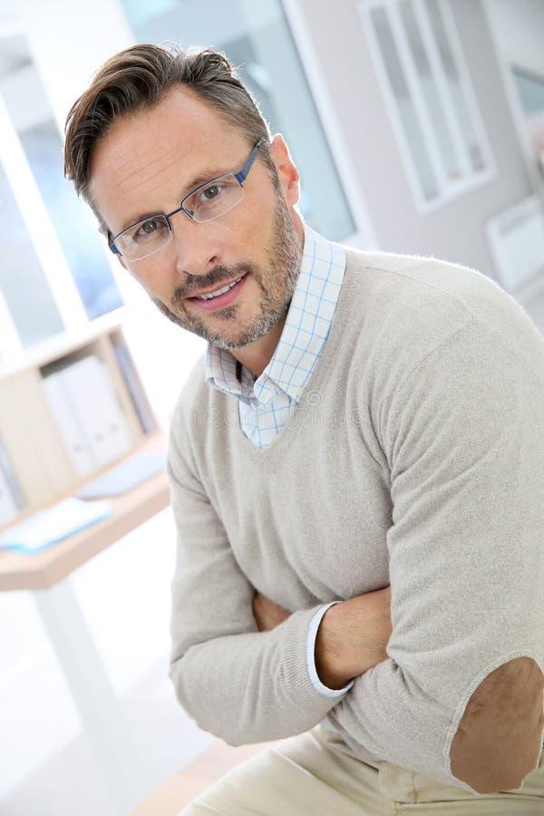 Stilvoller Mann von mittlerem Alter, der im Büro steht lizenzfreie stockbilder