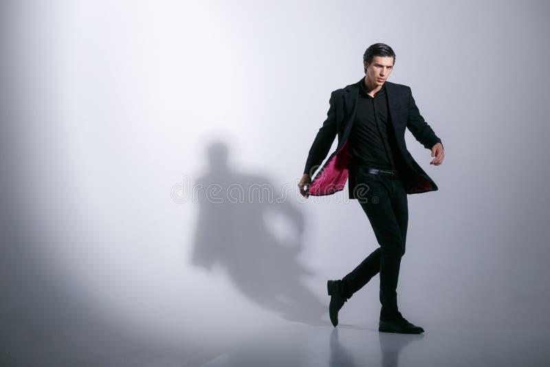 Stilvoller Mann, wirft elegantes im vollen Kostüm im Studio auf, lokalisiert auf einem weißen Hintergrund Horizontal schoss zuhau stockbilder