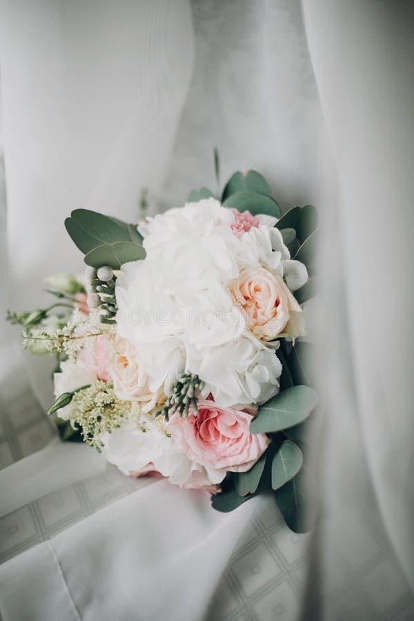 Stilvoller moderner Heiratsblumenstrauß auf weißem Tulle im weichen Licht im Hotelzimmer Morgenvorbereitung vor Heiratszeremonie  lizenzfreie stockfotos
