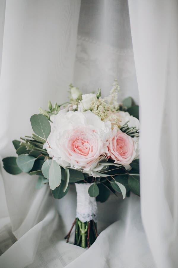Stilvoller moderner Heiratsblumenstrauß auf weißem Tulle im weichen Licht im Hotelzimmer Morgenvorbereitung vor Heiratszeremonie  stockbild