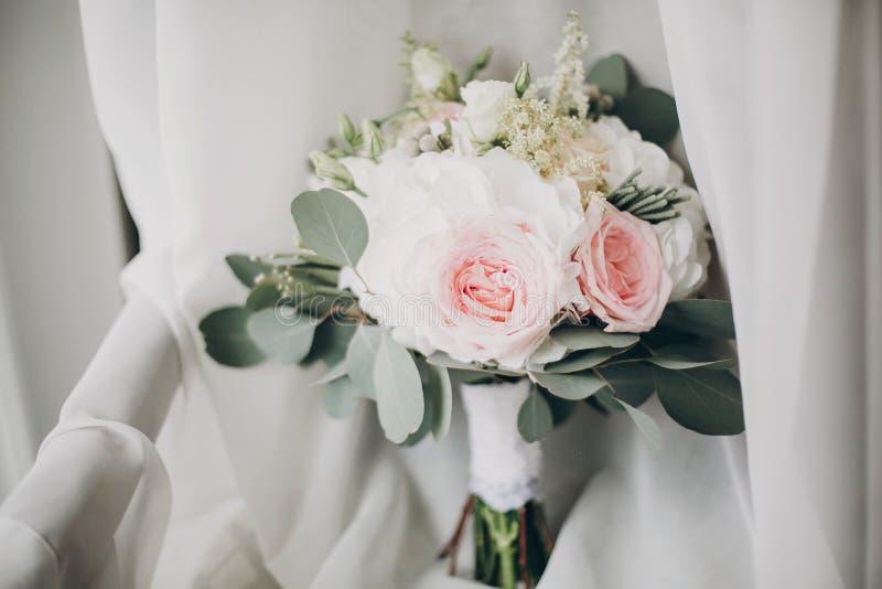 Stilvoller moderner Heiratsblumenstrauß auf weißem Tulle im weichen Licht im Hotelzimmer Morgenvorbereitung vor Heiratszeremonie  lizenzfreie stockbilder