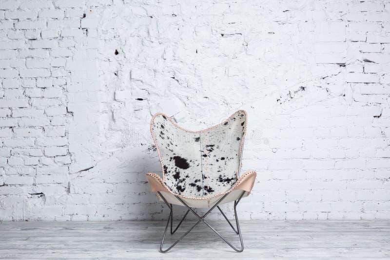 Stilvoller moderner Stuhl mit Tierdruck im Dachbodeninnenraum lizenzfreie stockfotografie