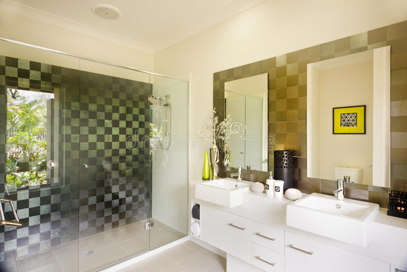 Stilvoller moderner Waschraum mit einer Glasdusche und Spiegeln stockbilder