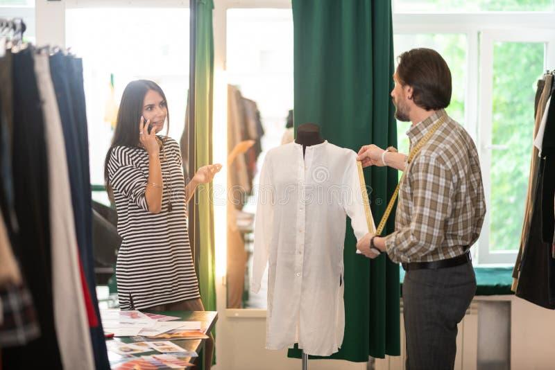 Stilvoller reizend beschäftigter schöner Modedesigner, der am Telefon spricht lizenzfreie stockbilder