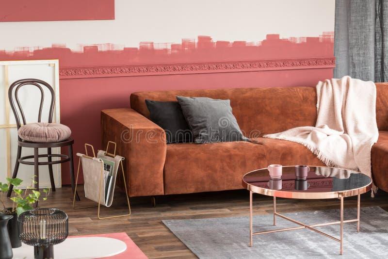 Stilvoller runder Couchtisch mit Blumen im kleinen Topf und in den Teeschalen im modernen Wohnzimmerinnenraum lizenzfreie stockfotografie