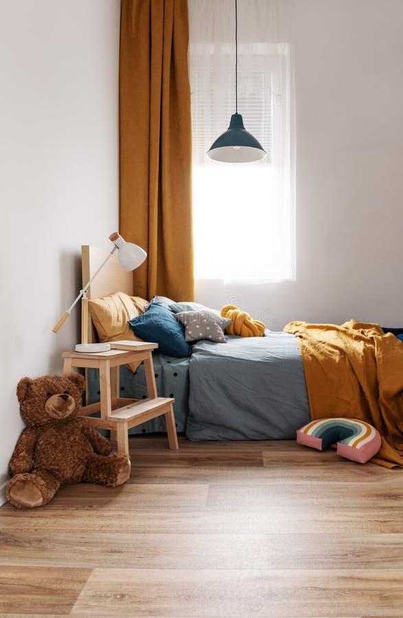 Stilvoller Schlafzimmerentwurf des blaues und orange Kindes in der hellen Wohnung stockfotos